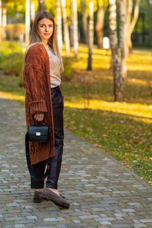 Stylish young woman in a knitted coat carrying a handbag turning to smile at the camera as she walks through an autumn park Reklamní fotografie - 133830917