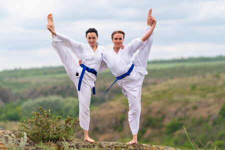 Two young woman doing synchronised acro yoga or acrobatic yoga balancing on one leg arm in arm in a rural landscape