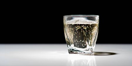 Cold effervescent drink in a glass or tumbler on a reflective bar counter viewed low angle on a black background with copy space