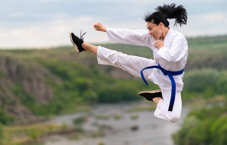 Young female kickboxer training outdoors leaping in the air with arm and leg extended against a rural river background
