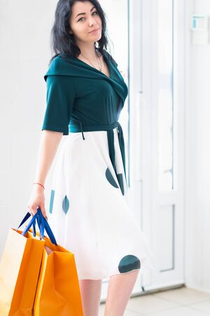 Stylish woman carrying orange shopping bags in a high key store as she turns to smile at the camera in a close up cropped portrait