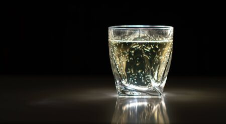 Sparkling drink or beverage in a glass or tumbler with selective lighting on a dark reflective surface with copy space Imagens