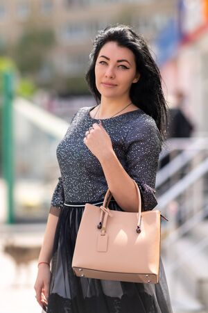 Attractive woman with handbag posing outdoors in town turning to look thoughtfully at the camera Archivio Fotografico