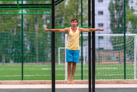 Strong muscular athletic young man hanging suspended from nets at an outdoor gym with straight outstretched arms in a health and fitness or active lifestyle concept