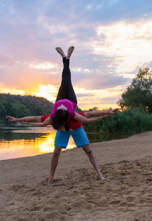 Young couple practicing yoga at sunrise on a beach in an elegant acrobatics pose with the young woman supported on the mans back in a health and fitness or active lifestyle concept