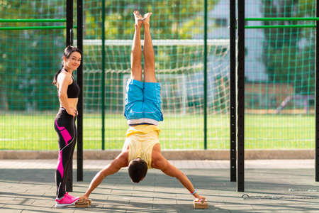 Muscular young man performing handstands using floor handles for support watched by a female personal trainer at an outdoor gym in a health and fitness or active lifestyle concept