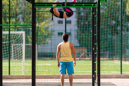 Young woman working out on ladder bars at an outdoor gym or sports facility watched by a personal trainer in a health and fitness concept Stock fotó