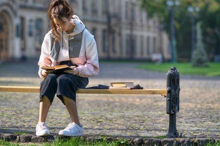 Trendy young teenage girl sitting studying on a bench in a park reading a book with copyspace and historic building background