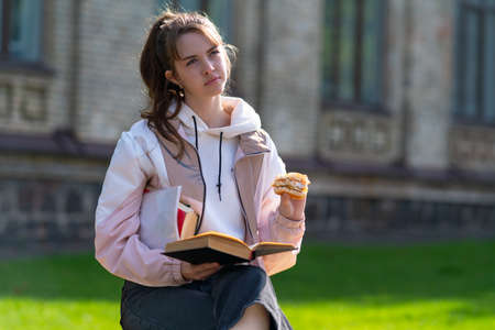 Young woman deep in thought sitting studying outdoors in evening sunshine while snacking on refreshments looking up with a contemplative expression