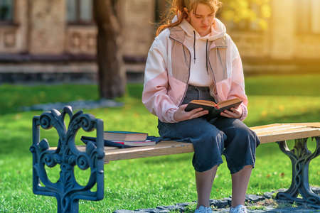 Close up on a young girl reading a book in a park relaxing in the warm autumn sunshine on a wrought iron bench