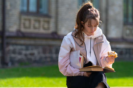 Young teenage girl snacking on a sandwich outdoors in an urban park as she sits on a bench reading or studying from a book