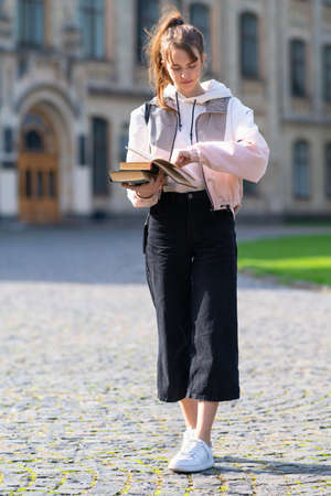Teenage girl concentrating on reading a handheld book as she walks across a quadrangle or urban park approaching the camera