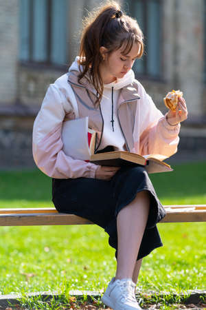 Young girl snacking on a sandwich while studying outdoors on a park bench in autumn sunshine with her books under her arm 스톡 콘텐츠