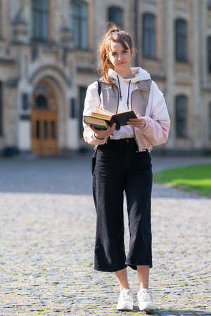 Young woman walking towards the camera outdoors with a quiet friendly smile and a bag over her shoulder carrying books on a college or university campus