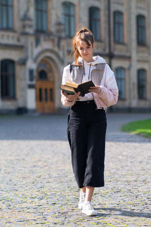 Young woman reading from handheld books while walking across a quadrangle or park outdoors in warm evening sunshine in autumn