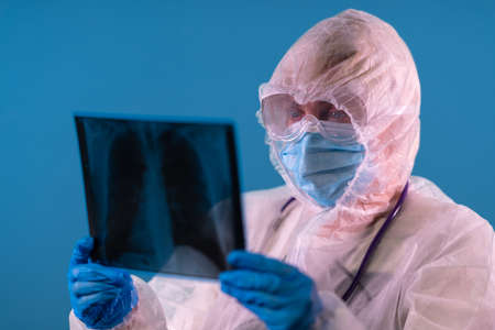 Doctor in a PPE suit is looking at X-ray of lungs