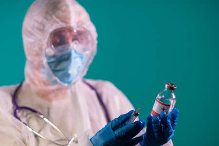 Female doctor in a PPE suit with a stethoscope on her shoulder is holding a syringe and vaccine in blue nitrile gloves