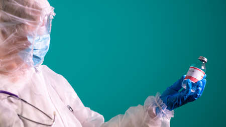A doctor in a PPE suit with a stethoscope on her shoulder is holding a COVID-19 vaccine. 스톡 콘텐츠