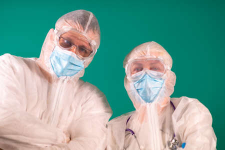 Two physicians with face shields in PPE suit uniforms wearing medical protective Masks