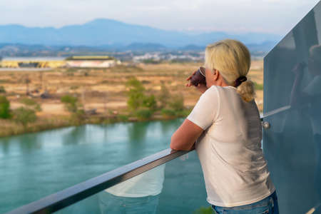Woman standing on an elevated outdoor balcony sipping coffee as she surveys the river or lake below and rural landscape with copyspace 스톡 콘텐츠