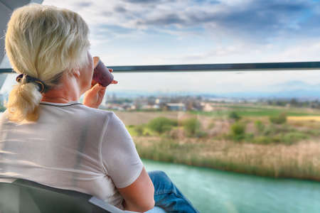 Woman sitting enjoying a drink on an outdoor patio facing out through a glass balustrade overlooking the river and countryside below in an over the shoulder view
