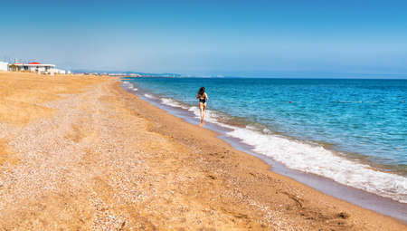 Shapely woman in swimsuit jogging along a tropical beach at the edge of the surf in warm evening light towards a distant city in a travel and vacation concept 스톡 콘텐츠