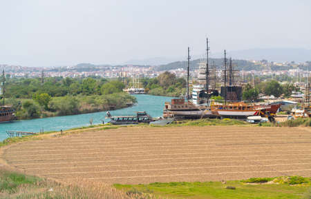 Tall ships and tourist boats moored along a winding river with a view over a ploughed field to a distant city on a hazy day 스톡 콘텐츠