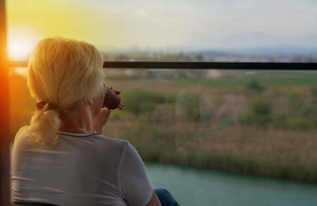 Woman sipping coffee on a balcony at sunrise overlooking a river with the fiery orb of the sun peeping over her shoulder and copyspace