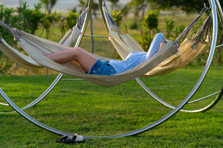 Woman relaxing in a modern hammock on a metal frame in the garden in evening light with her arm obscuring her face and copyspace 스톡 콘텐츠