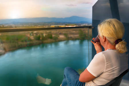Woman sitting sipping coffee on a balcony at sunrise overlooking a lake or river below with a view to distant mountains