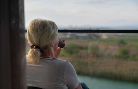 Woman sitting enjoying a quiet drink on an outdoor balcony as she surveys the landscape below through a glass balustrade in an over the shoulder view