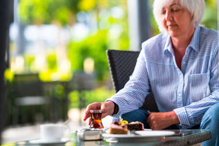Woman enjoying a mug of hot tea and cakes on a patio of an outdoor restaurant in a cropped view as she reaches for the beverage with copyspace