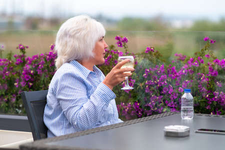 Attractive middle-aged woman relaxing on an outdoor patio or balcony in spring with a glass of cold white wine looking away over colorful bougainvillea flowers