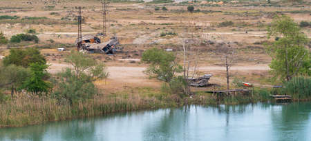 Panorama view of a dilapidated building between pylons with outbuildings an the shoreline of a lake or river with reflections of surrounding trees