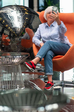 Woman taking a selfie in front of a silver metallic ball sculpture in a vestibule as she relaxes in a comfy orange tub chair 스톡 콘텐츠