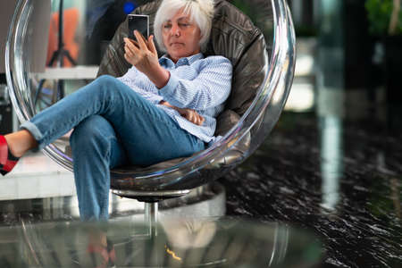 Woman engrossed in watching media on her smartphone relaxing in a modern transparent perspex tub chair in a vestibule
