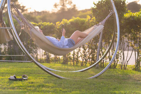 Woman relaxing with her mobile phone in a hammock on a circular metal frame outdoors in a garden by the warm glow of the setting sun