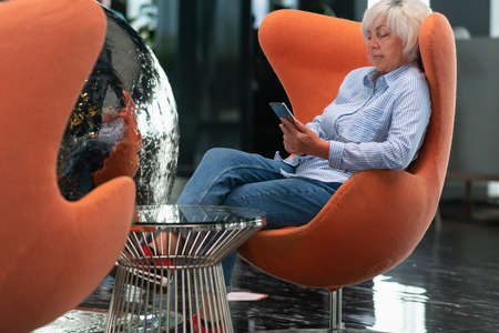 Woman relaxing in a colorful tub chair using her mobile phone reflected in a silver orb sculpture alongside with copyspace