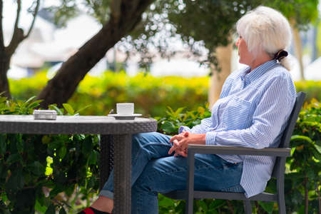 Pensive woman relaxing on an outdoor patio at a restaurant table with a cup of tea as she stares out over the lush leafy green plants at the scene outside