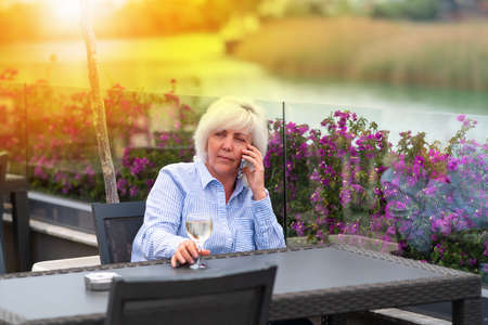 Woman sitting relaxing enjoying sundowners of chilled white wine on an outdoor patio backlit by the warm glow of the setting sun as she chats on her mobile phone