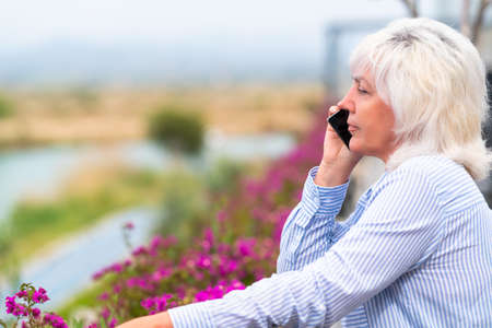 Thoughtful middle-aged woman listening to a phone call on her mobile as she stands on an outdoor balcony with colorful purple bougainvillea flowers 스톡 콘텐츠