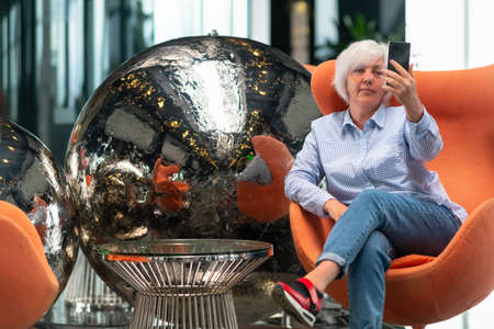 Woman relaxing in a tub chair in front of a modern metallic silver sculpture or circular balls taking a selfie on her mobile phone