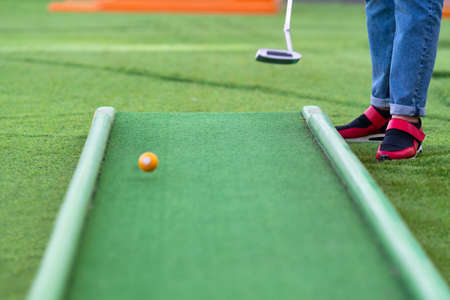 Person putting the ball with a club while playing a game of miniature golf on an outdoor course with artificial green turf in a low angle anonymous view with copyspace
