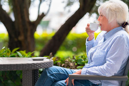 Attractive trendy middle-aged woman relaxing with a cup of coffee or tea at a table in the garden in a close up cropped low angle view