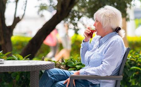 Woman sipping a glass of hot tea on an outdoor patio as she spends a relaxing day watching people walk by behind tropical plants 스톡 콘텐츠