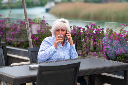 Woman seated at a restaurant overlooking a river chatting on her mobile phone as she sips a chilled glass of white wine with copyspace 스톡 콘텐츠