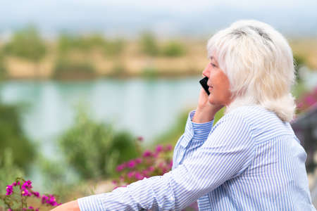 Woman standing on an outdoor balcony chatting on her mobile phone with a quiet smile as she overlooks a lake below in close up with copyspace 스톡 콘텐츠