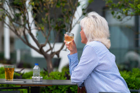 Woman relaxing at an outdoor restaurant enjoying a glass of chilled white wine in a close up low angle view as she looks away 스톡 콘텐츠
