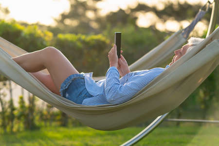 Woman relaxing on a comfortable hammock outdoors in a garden watching media or reading a message on her mobile phone in a close up side view in evening light 스톡 콘텐츠
