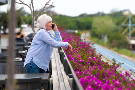 Woman standing on the outdoor patio of a restaurant leaning on the balustrade chatting on her mobile phone with colorful purple spring bougainvillea flowers
